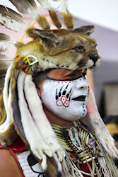 This was the most incredible headdress.  The cat was so angry, his ears at attack mode, his nose wrinkled in aggression, mouth open, teeth showing and eyes focused on his prey. While the face of the Native American is painted with Bear Track which depending on his tribe can mean many things and conveys a message of leadership and authority. Makes sense as to why he has on this headdress of the angry cat. At any rate they both are just incredible.